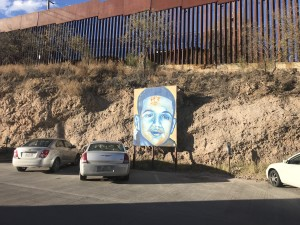 A mural of Jose Antonio Rodríguez sits in front of the border fence.